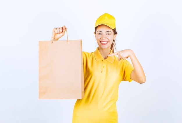 Kobieta kurier trzyma kartonową torbę na zakupy i uczucie szczęścia.