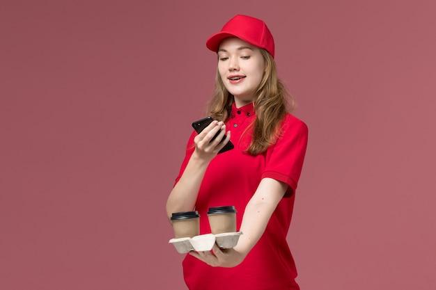 Kobieta kurier w czerwonym mundurze robi zdjęcie filiżanek kawy na różowym, jednolita usługa dostarczająca pracownik