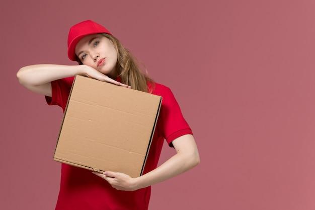 Kobieta kurier w czerwonym mundurze trzyma pudełko z dostawą żywności na jasnoróżowym, jednolitym pracownika służby pracy dziewczyna dostawy