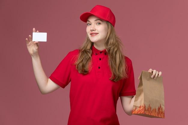Kobieta kurier w czerwonym mundurze, trzymając białą kartę na różowym, jednolitym dostawie usług