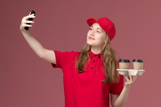 Kobieta kurier w czerwonym mundurze, trzymając brązowe filiżanki kawy dostawy, biorąc selfie na różowym, jednolitym pracowniku usługowym