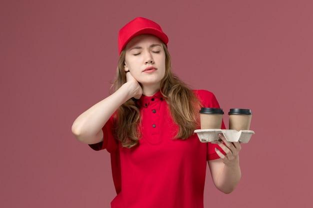 Kobieta kurier w czerwonym mundurze, trzymając brązowe filiżanki kawy z bólem szyi na różowym, jednolita praca pracownika dostawy usług