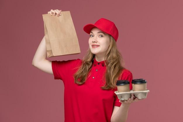Kobieta kurier w czerwonym mundurze, trzymając brązowe kubki do kawy i pakiet żywności na różowym, jednolity pracownik dostawy usług