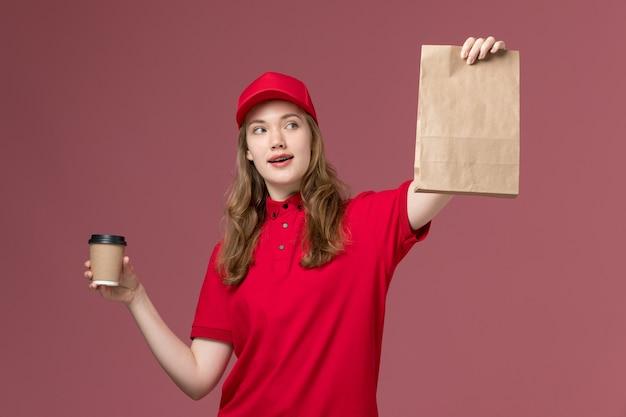 Kobieta kurier w czerwonym mundurze, trzymając dostawę filiżankę kawy i pakiet żywności na jasnoróżowym, jednolitym pracownika służby pracy