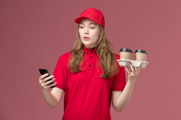 Kobieta kurier w czerwonym mundurze, trzymając filiżanki do kawy i używając swojego telefonu na różowym, jednolitym zadaniu dostawy usług