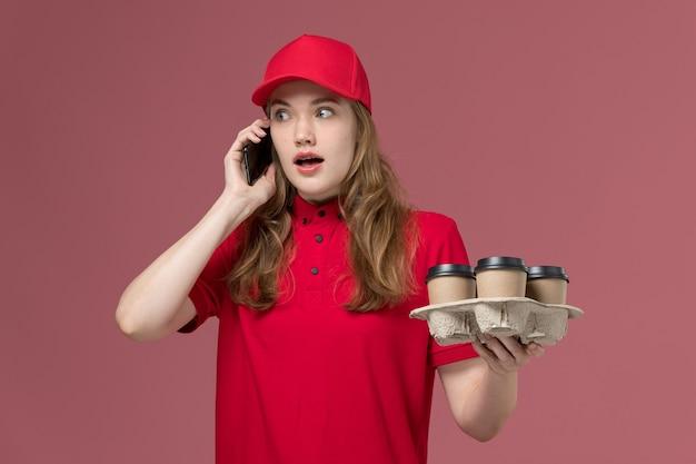 Kobieta kurier w czerwonym mundurze trzymając kawę rozmawia przez telefon na jasnoróżowym, mundurze służbowym dostawa usług pracownika