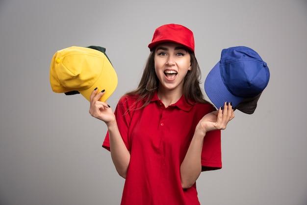 Kobieta kurier w czerwonym mundurze trzymając kolorowe czapki.
