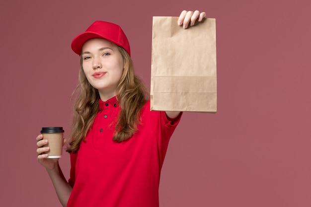 Kobieta kurier w czerwonym mundurze, trzymając pakiet żywności i kawę na różowym, jednolitej pracy pracownika dostawy usług