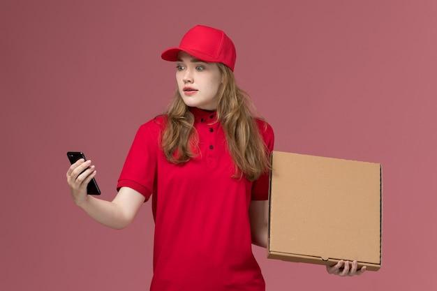 Kobieta kurier w czerwonym mundurze, trzymając pudełko z jedzeniem i używając swojego telefonu na różowym, jednolitym pracowniku świadczącym usługę
