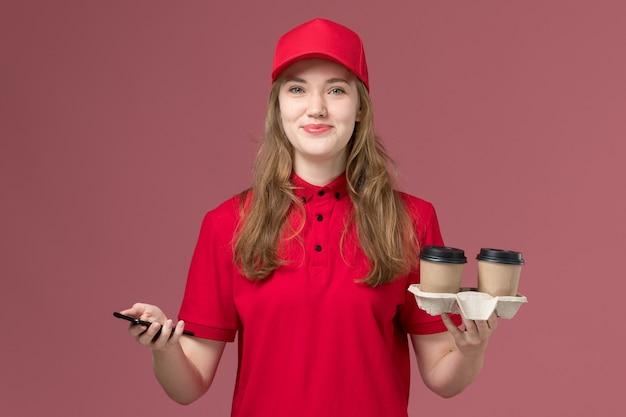 Kobieta kurier w czerwonym mundurze, trzymając smartfon i filiżanki kawy na różowym, jednolitym pracowniku dostawy usług