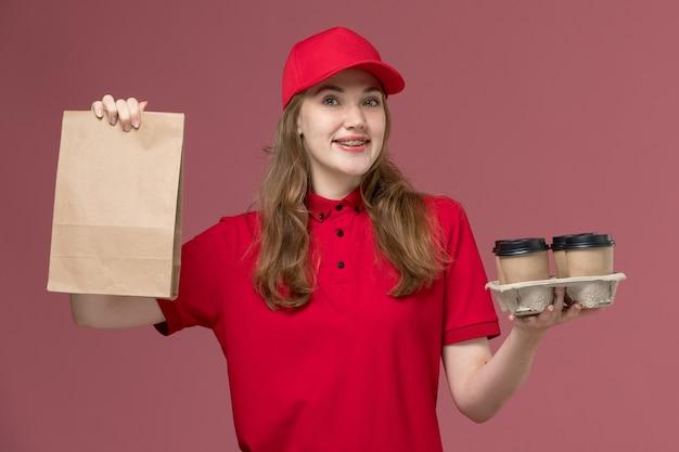 Kobieta kurier w czerwonym mundurze uśmiechnięty, trzymając brązowe filiżanki kawy dostawy i pakiet żywności na różowym, jednolity pracownik dostawy usług