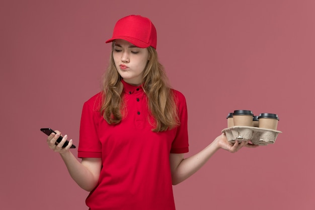 Kobieta kurier w czerwonym mundurze za pomocą swojego smartfona, trzymając filiżanki kawy na różowym, jednolitym pracowniku dostawy usług