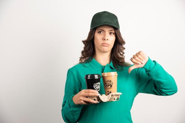 Kobieta kurier w mundurze trzymając kawę na wynos i pokazując kciuk w dół.