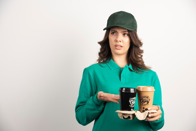Kobieta kurier w mundurze trzymając kawę na wynos.