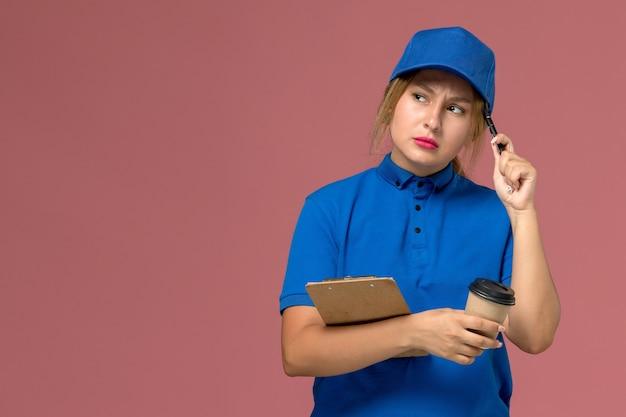 Kobieta kurier w niebieskim mundurze pozuje trzymając filiżankę kawy i notatnik z myślącym wyrazem na różowym, jednolita dostawa usług