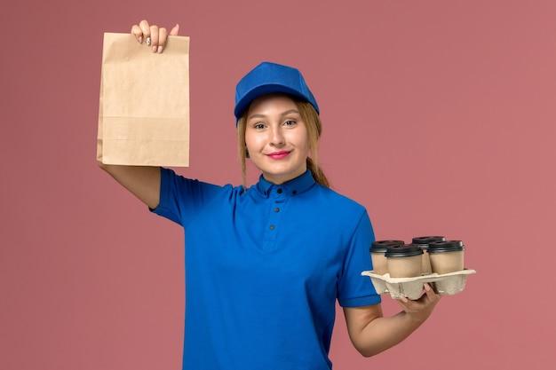 Kobieta kurier w niebieskim mundurze, trzymając opakowanie żywności i brązowe filiżanki kawy na jasnoróżowym, mundurze usługowym