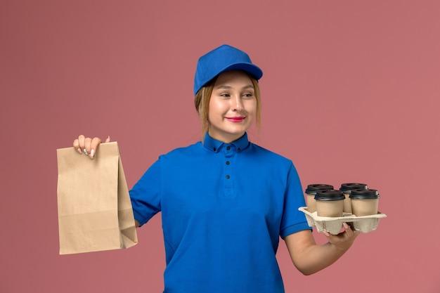 Kobieta kurier w niebieskim mundurze, trzymając pakiet żywności i brązowe filiżanki kawy na różowo, mundurowy pracownik dostawy