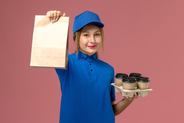 Kobieta kurier w niebieskim mundurze trzymając pakiet żywności i brązowe filiżanki kawy z uśmiechem na różowo, mundurowy pracownik dostawy