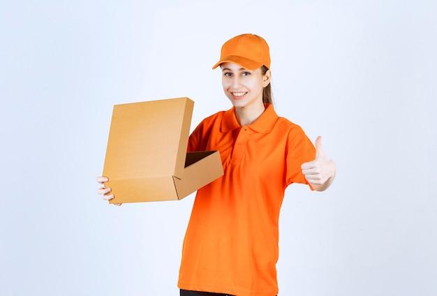 Kobieta kurier w pomarańczowym mundurze trzyma otwarty karton i pokazuje pozytywny znak ręki.