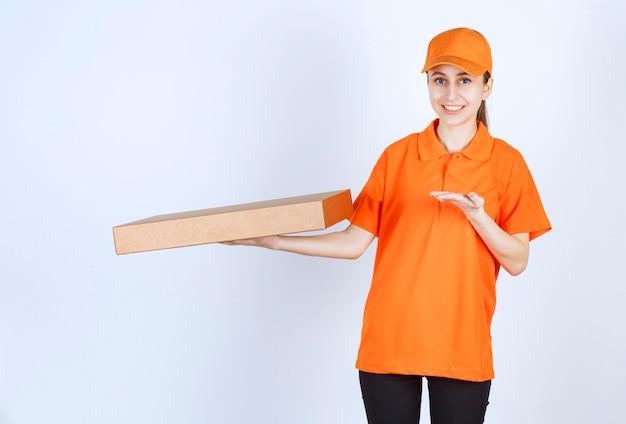Kobieta kurier w pomarańczowym mundurze trzyma pudełko pizzy na wynos.
