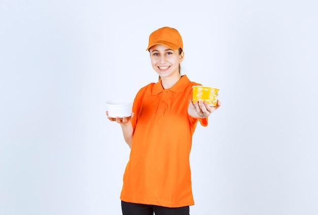 Kobieta kurier w pomarańczowym mundurze, trzymając w obu rękach plastikowy i żółty kubek z makaronem.