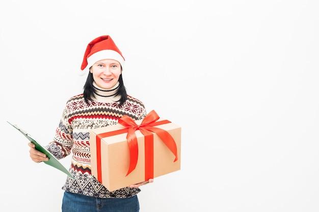 Kobieta kurier w santa hat i świątecznym swetrze trzyma prezent