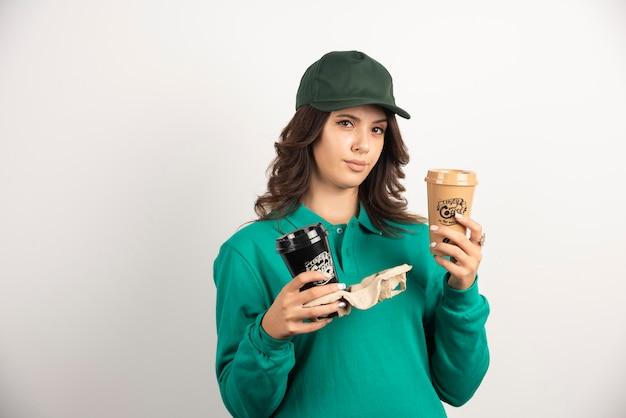 Kobieta kurier w zielonym mundurze trzymając filiżanki kawy z poważnym wyrazem twarzy.