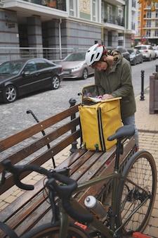 Kobieta kurier wypełniając dokumenty na zewnątrz w kasku rowerowym