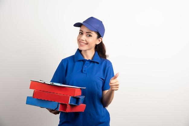 Kobieta kurier z kartonem pizzy i schowka. zdjęcie wysokiej jakości