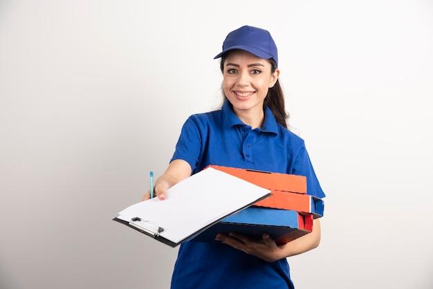 Kobieta kurier z kartonu pizzy dając schowka. zdjęcie wysokiej jakości