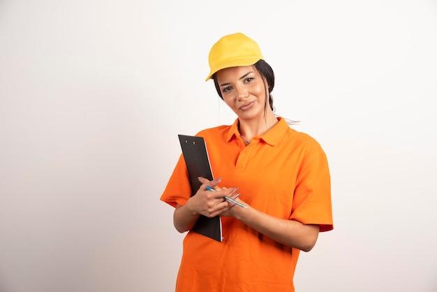 Kobieta kurier z ołówkiem i schowkiem na białej ścianie.
