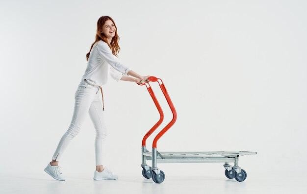 Kobieta kurier z wózkiem cargo na lekkiej przestrzeni w pełnym wzroście