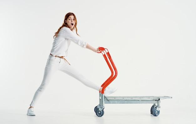 Kobieta kurier z wózkiem cargo na świetle