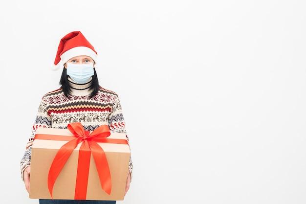 Kobieta kurierka w czapce mikołaja i masce medycznej trzyma prezent