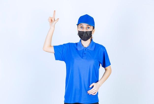 Kobieta kurierka w masce i niebieskim mundurze przedstawiająca coś z tyłu.
