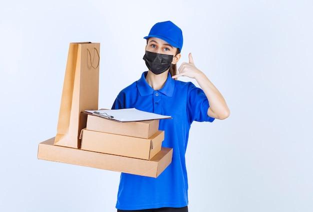 Kobieta kurierka w masce i niebieskim mundurze trzyma kartonową torbę na zakupy i wiele pudełek, prosząc o telefon.