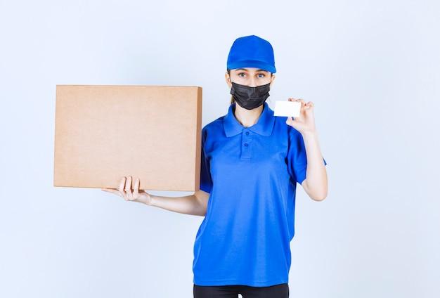 Kobieta kurierka w masce i niebieskim mundurze trzymająca dużą kartonową paczkę i prezentująca swoją wizytówkę.