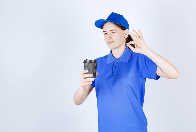 Kobieta kurierka w niebieskiej koszulce mruga, robiąc znak ręką, trzymając kawę przed białą ścianą