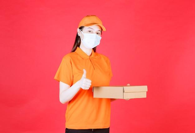 Kobieta kurierka w pomarańczowym mundurze i masce trzyma karton i pokazuje pozytywny znak ręki.