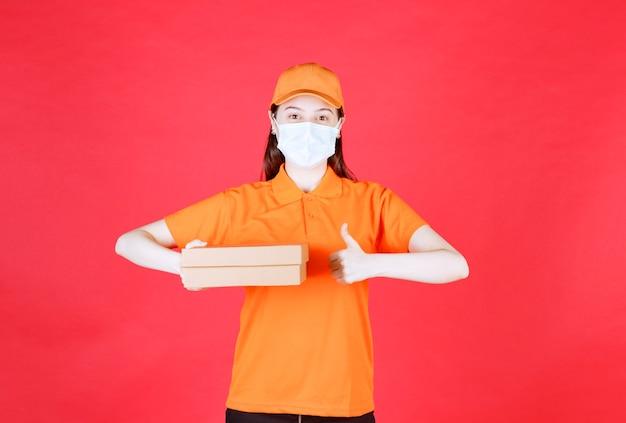 Kobieta Kurierka W Pomarańczowym Mundurze I Masce Trzyma Karton I Pokazuje Pozytywny Znak Ręki. Premium Zdjęcia