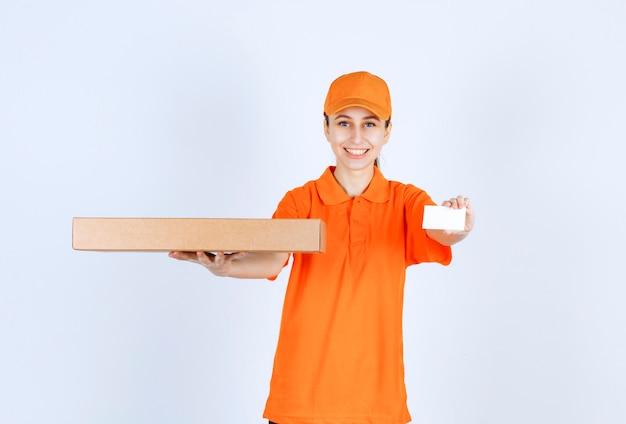 Kobieta kurierka w pomarańczowym mundurze trzyma pudełko pizzy na wynos i przedstawia swoją wizytówkę.