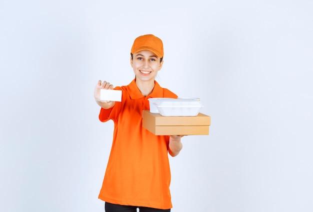 Kobieta kurierka w pomarańczowym mundurze trzymająca karton i plastikowe pudełko na wynos podczas prezentacji wizytówki.