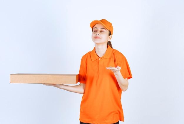 Kobieta kurierka w pomarańczowym mundurze trzymająca pudełko pizzy na wynos i wąchająca produkt.