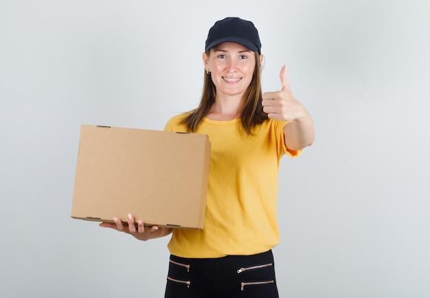 Kobieta kurierka w t-shirt, spodnie, czapkę trzymająca karton z kciukiem do góry i wyglądająca na zadowoloną