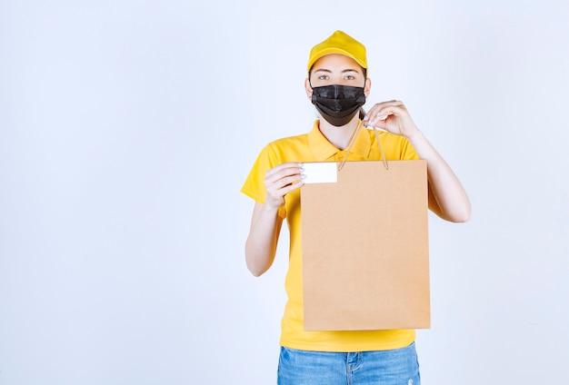 Kobieta kurierka w żółtej koszulce pokazuje swoją wizytówkę, trzymając torbę przed białą ścianą