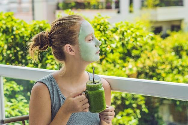 Kobieta kurort stosowania twarzy zielonej maski glinki. zabieg upiększający. świeży zielony smoothie z bananem i szpinakiem z sercem z sezamu. miłość do zdrowej koncepcji surowej żywności. koncepcja detoksu