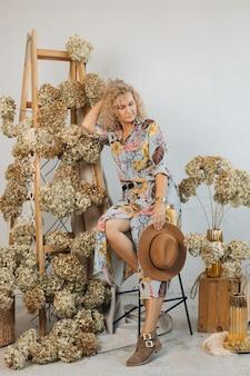 Kobieta kwiaciarnia w sukience wygląda i marzy. piękna kompozycja kwiatowa z przepięknymi suszonymi kwiatami hortensji, w stylowej przestrzeni, na drewnianych schodach.