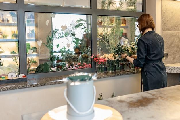 Kobieta kwiaciarnia wybiera kwiaty, aby stworzyć bukiet kwiatów. pudełko na kwiaty jako prezent na uroczystość. koncepcja oryginalnych prezentów.
