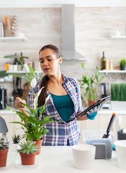 Kobieta kwiaciarnia za pomocą tabletu do ogrodnictwa dotykając kwiat w domowej kuchni