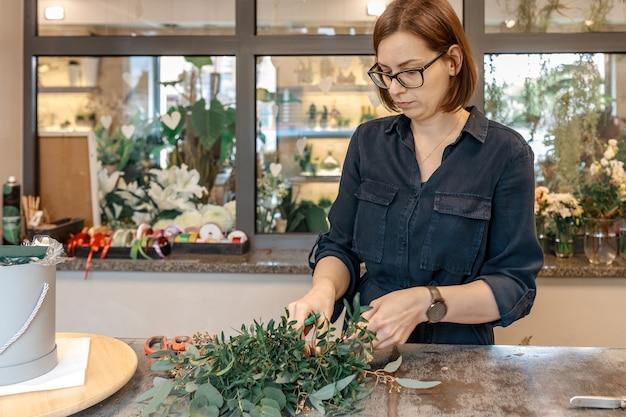 Kobieta kwiaciarnia zbiera bukiet kwiatów w swoim warsztacie. bukiet w pudełku. koncepcja oryginalnych prezentów.